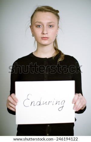 Portrait of a real young woman on a light background in a black cardigan with the sign in her hands. Shallow depth of field. Focus on the eyelashes - stock photo