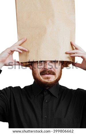 Portrait of a red-bearded, balding male brutal. White isolated background. Black shirt and pants. Paper bag over head. looks out of the package, closeup - stock photo