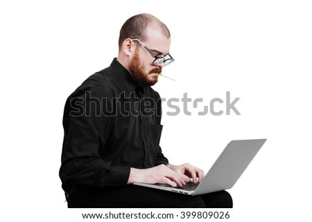 Portrait of a red-bearded, balding male brutal. White isolated. Man in a black shirt pants.  Sitting with laptop.  Grandma's glasses. nervously smoking. Side view.  Office employee.