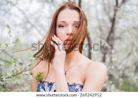 Portrait of a red-haired pretty young woman in spring orchard between blooming apricot trees. Hair moving from wind - stock photo