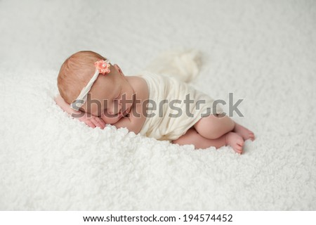 Portrait of a red headed, 2 week old, newborn baby girl. She is wrapped in white material and sleeping on a white, gauzy blanket.