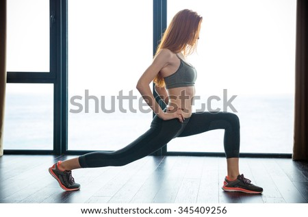 Portrait of a redhead fitness woman doing warm up exercises  - stock photo