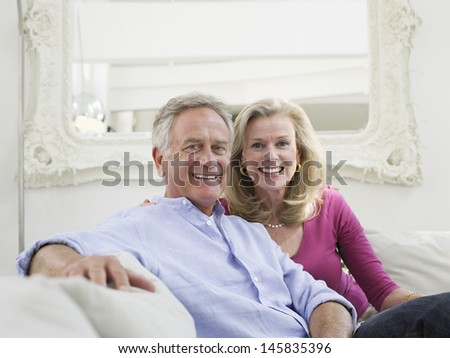 Portrait of a relaxed and smiling mature couple in white home interior - stock photo