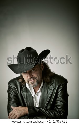 Portrait of a relaxed cowboy smirking at the camera. - stock photo
