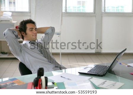 Portrait of a relaxed man in front of a laptop computer - stock photo