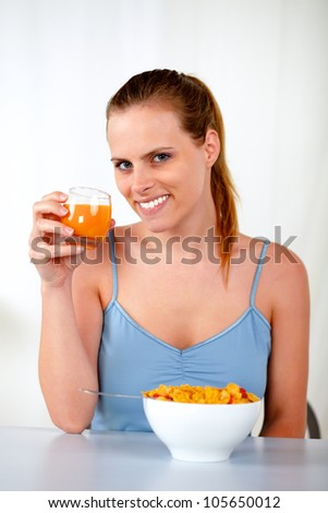 Portrait of a relaxed pretty young woman at breakfast at home indoor - stock photo