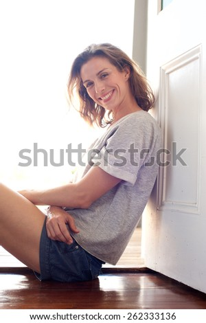 Portrait of a relaxed smiling woman sitting on wooden floor at home