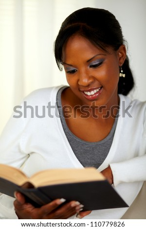 Portrait of a relaxed woman reading a book at soft colors composition
