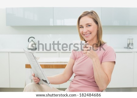 Portrait of a relaxed woman with newspaper having coffee in the kitchen at home