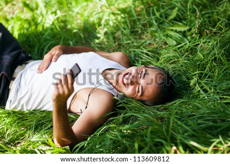 Portrait of a relaxed young male listening to music on headphone while lying in a park - Outdoor - stock photo