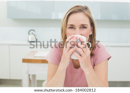 Portrait of a relaxed young woman having coffee in the kitchen at home