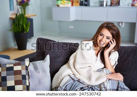 Portrait of a relaxed young woman text messaging on sofa in living room at home