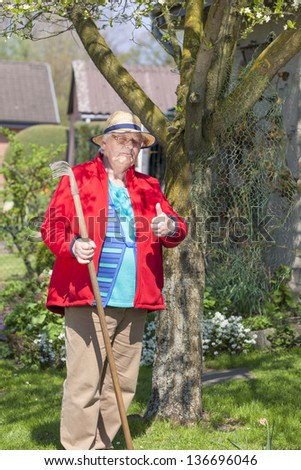 Portrait of a retired woman working in the garden and doing spring garden work. - stock photo