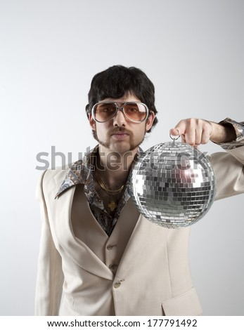 Portrait of a retro man in a 1970s leisure suit and sunglasses holding a disco ball - stock photo
