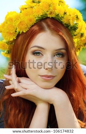 Portrait of a romantic young woman in a circlet of flowers outdoors. - stock photo