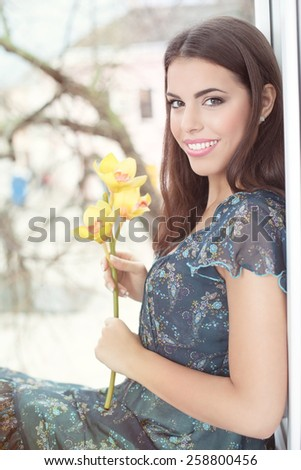Portrait of a romantic young woman sitting in front of a window and smiling at the camera.