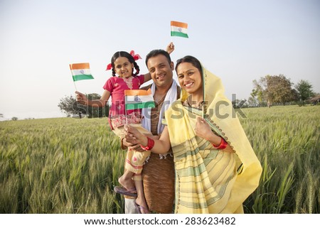 Portrait of a rural family holding an Indian flag - stock photo