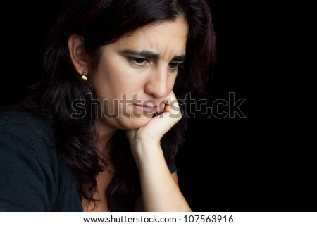 Portrait of a sad and depressed hispanic woman with a thoughtful expression isolated on black - stock photo