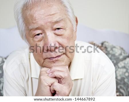 portrait of a sad asian senior man. - stock photo