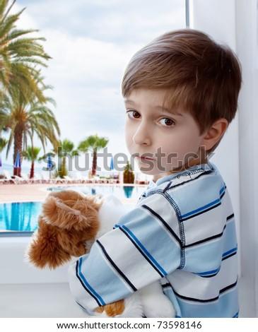 Portrait of a sad boy against the window - stock photo