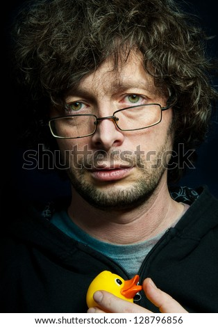 portrait of a sad man with broken glasses and duck toy - stock photo