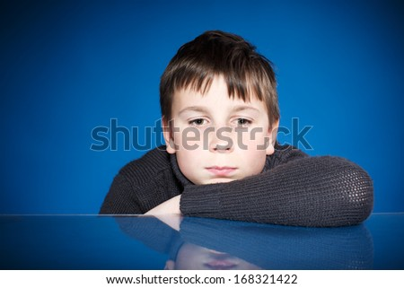 Portrait of a sad teenager on a blue background - stock photo