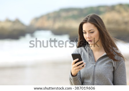 Portrait of a sad teenager walking on the beach is checking online the mobile phone waiting for a message in a rainy day - stock photo