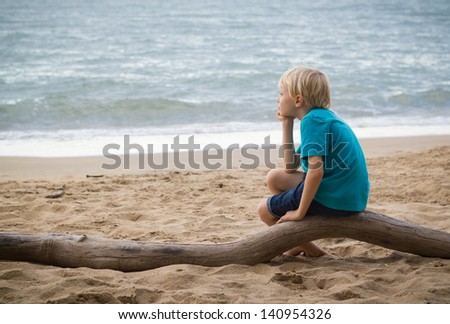 Portrait of a sad young boy thinking on the beach with copy-space. - stock photo