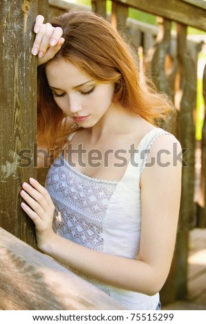 Portrait of a sad young girl who relies on the wooden wall - stock photo