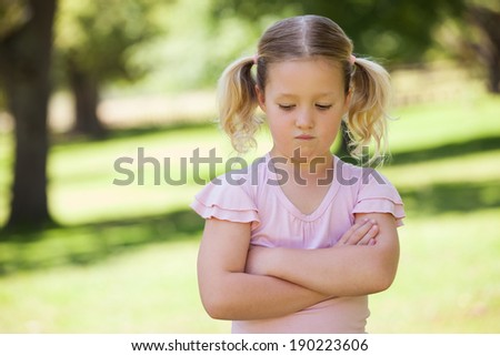 Portrait of a sad young girl with arms crossed at the park - stock photo