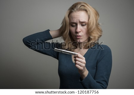 portrait of a sad young woman looking at pregnancy test with bad news - stock photo