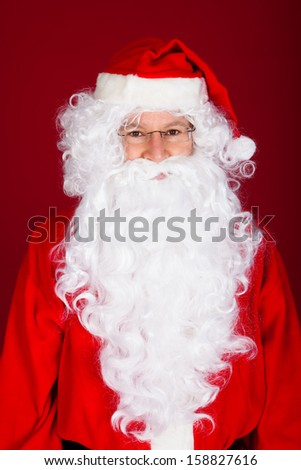 Portrait of a Santa Claus over red background