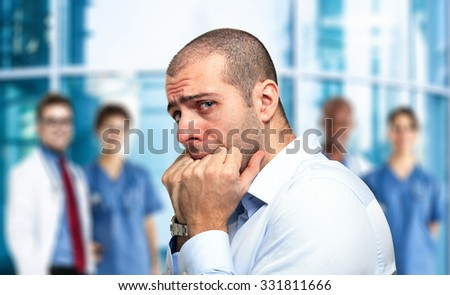 Portrait of a scared guy in front of an hospital - stock photo