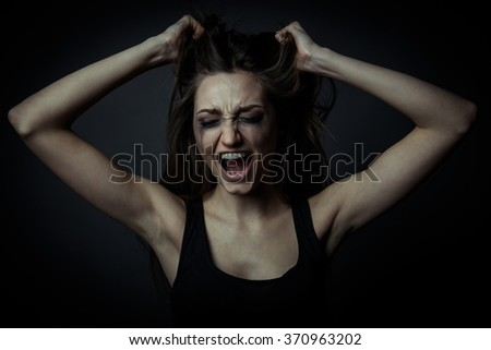 Portrait of a scared screaming girl, hands on the forehead