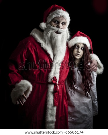portrait of a scary looking santa claus and an elf - stock photo