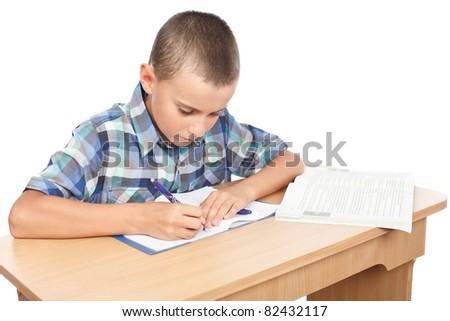 Portrait of a school boy doing homework at his desk, isolated on white background