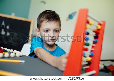 Portrait of a school boy learning maths with an abacus