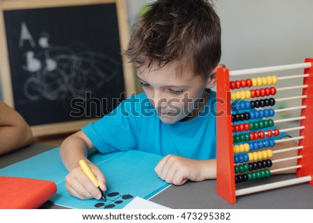 Portrait of a school boy working on math homework with an abacus
