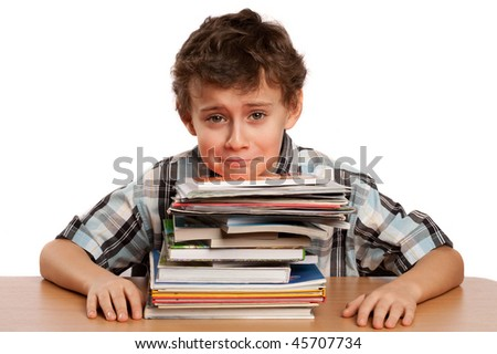 Portrait of a schoolboy overwhelmed by the stack of books on his desk