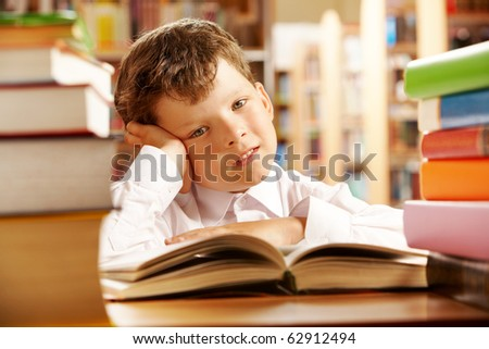 Portrait of a schoolboy sitting at table piled with books