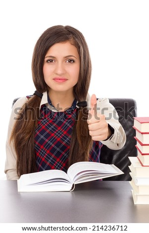 Portrait of a schoolgirl sitting at her desk with an open book and showing thumb up  isolated on white background  - stock photo