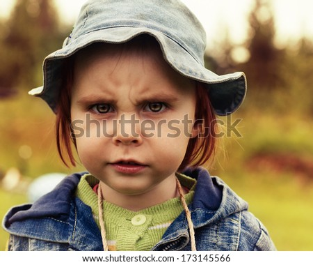Portrait of a scowling baby. - stock photo