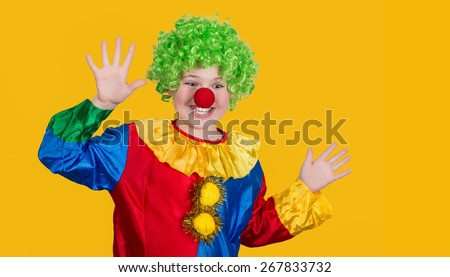Portrait of a screaming clown with copyspace on yellow background. Funny kid in green wig in clown costume. - stock photo