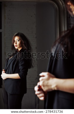 Portrait of a seductive young woman looking into the mirror - stock photo