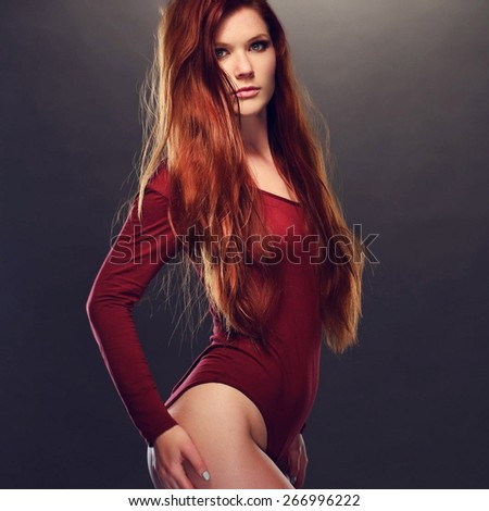 Portrait of a Seductive Young Woman with Long Blond Hair Posing in Red Long Sleeved Leotard with Hands on her Waist While Looking at the Camera. Captured in Studio with Gray Brown Background. - stock photo