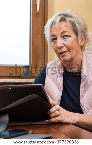 portrait of a senior adult with tablet and smartphone