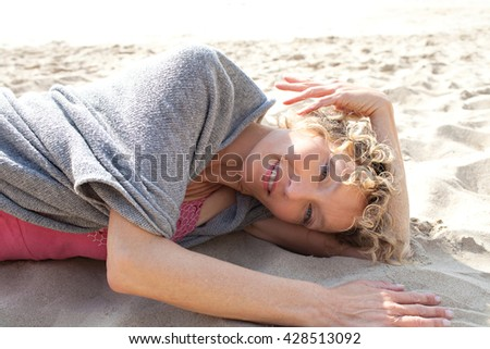 Portrait of a senior beautiful woman laying down on a sandy beach shore, looking and smiling at camera on holiday, nature outdoors. Travel lifestyle and healthy living, sunny exterior. - stock photo