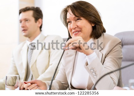 Portrait of a senior business woman bending speaks into the microphone - stock photo