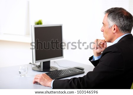 Portrait of a senior businessman working on computer at the office. - stock photo