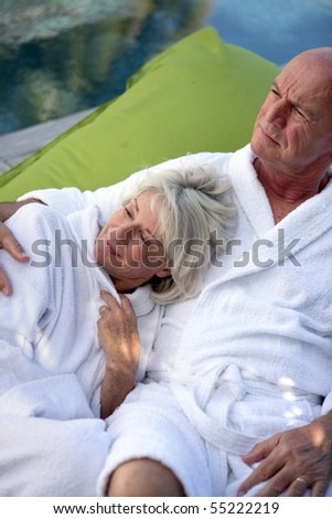 Portrait of a senior couple in bathrobe sitting on a deck chair - stock photo